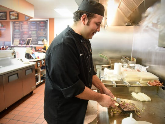 Chef Jorge Serna prepares a Dolsie's Lunchbox Grille classic, a shaved steak sandwhich, Wednesday, July 12, in downtown St. Cloud.