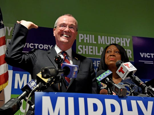 """Democratic gubernatorial nominee Phil Murphy """"raises the roof"""" while formally announcing Sheila Oliver as his running mate during a July press conference in Newark."""
