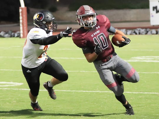 Mt Whitney's Zack Reza (10) rushes past Tulare Union's Andrew Ruelas during a non-league high school football game with Tulare Union at Mineral King Bowl
