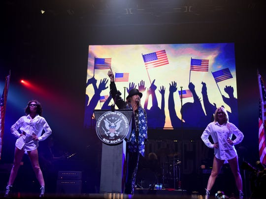 "Kid Rock gives a speech behind a ""United States of 'Merica"" podium during his performance at Little Caesars Arena in Detroit on Tuesday, Sept. 12, 2017. His appearance was met by dozens of protesters from a civil rights group. (Tanya Moutzalias/The Ann Arbor News-MLive.com Detroit via AP)"