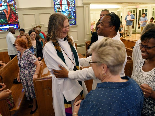 "Ardie Walser offers a peace greeting to Strand during services at St. Mark's Episcopal Church in Teaneck. In 2015, Strand wrote to her congregants at the First Presbyterian Church of Ridgefield Park about her transition: ""It has all been there hiding from view, dying to blossom, waiting only for my permission."""