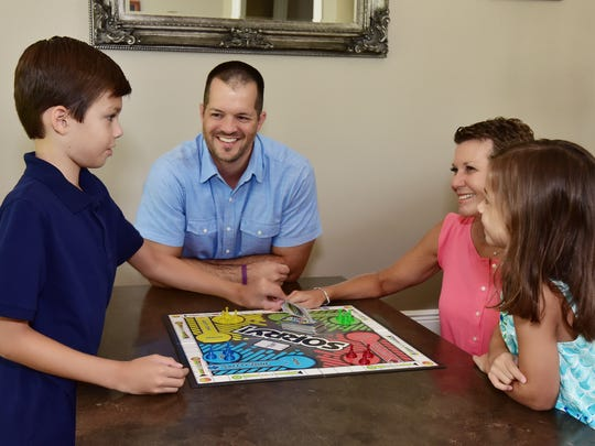 From left, Zachary, Travis, Tara and Abigail Peterson play a game as they enjoy some fun and relaxation.
