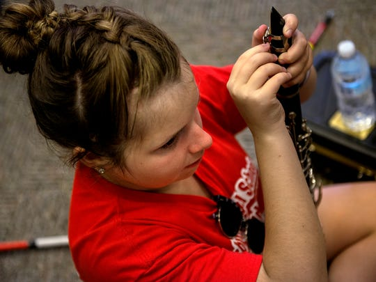 Autumn Michels prepares her clarinet in the school band room before taking the field to play during the homecoming football game against Fowler on Friday, Sept. 22, 2017, at Laingsburg High School.