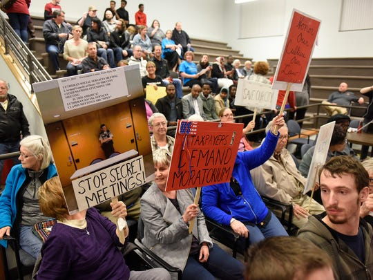 People hold signs before the start of the St. Cloud City Council meeting Monday, Oct. 23, at St. Cloud City Hall.
