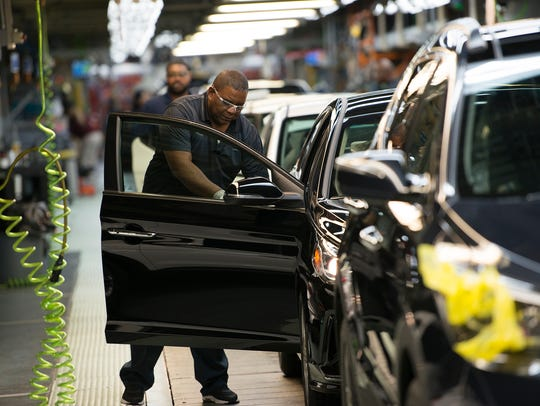 Hyundai employees work on cars on the assembly line