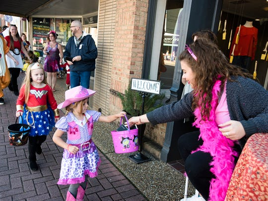 Maggie Glover, of Provision Clothing, hands out candy for in the Prattville Candy Walk on Monday, Oct. 30, 2017, in Prattville, Ala.