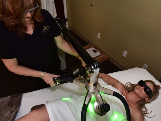 Teri Pitesa adjusts the Verju laser over a client,