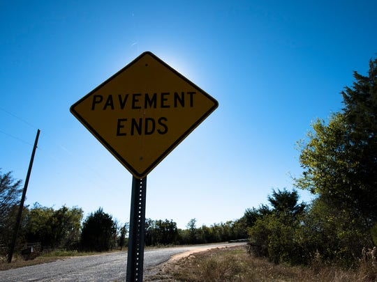 A sign warning drivers of the end of the roads pavement off of Sugar Berry Lake Road in Montgomery County, Ala., on Oct. 26, 2017.