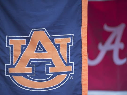 A tailgate hangs both Auburn and Alabama banners before