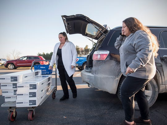 Stephanie Hunsberger, left, and Tracy Freleigh load