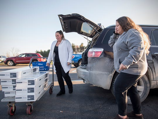 Stephanie Hunsberger, left, and Tracy Freleigh load their purchases into the back of their GMC Acadia in the Menard's parking lot. Sheriff Tim Donnellon is warning residents to be safe while holiday shopping.