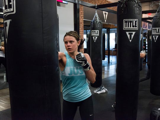 Madison Henry, 23, of Ann Arbor, works out during her class at the Title Boxing Club in Ann Arbor.