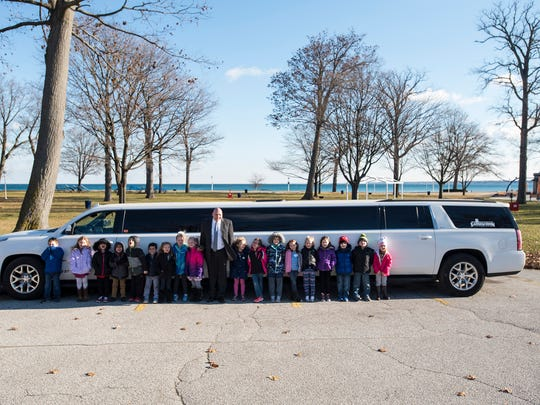 Keewahdin Elementary students stand next to a limousine at Lakeside Beach Wednesday. Students who raised $150 or more as part of the school's Husky Hustle fundraiser were given a ride in a limo to McDonald's and Lakeside Beach.