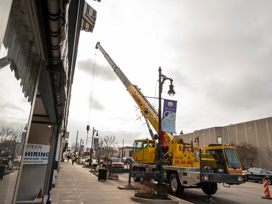 Crews from Raymond Excavating work to hang Christmas