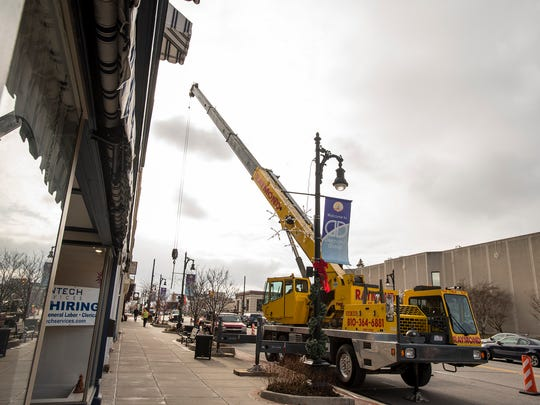 Crews from Raymond Excavating work to hang Christmas lights over Military Street in Port Huron Thursday.