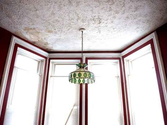 A light fixture hangs in front of windows in a living