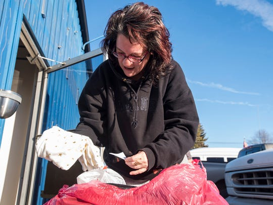 Lisa Bearden sorts through items in a bag of goods outside of the Salvation Army's distribution center in Port Huron Dec. 20. Bearden was picking up items for her daughter and her daughter's children.