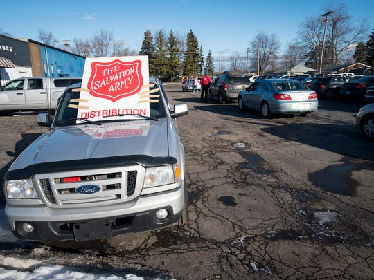 Cars fill the parking lot of the Salvation Army's distribution center on Lapeer Road in Port Huron Dec. 20.  Groups of people came in waves at assigned times to pick up bags, stocking stuffers, food goods and more.