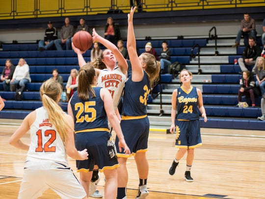Players from Capac High School block Marine City's Stephanie Abraham (21) during their SC4 Holiday Girls' Basketball Showcase match Dec. 28.