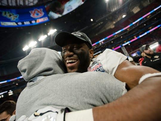 UCF wide receive Tre'Quan Smith (4) embraces a coach