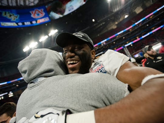 UCF wide receive Tre'Quan Smith (4) embraces a coach after UCF defeated Auburn 34-27 in the Peach Bowl on Monday, Jan. 1, 2018, at Mercedes-Benz Stadium in Atlanta, Ga.