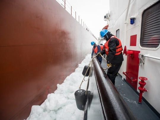 Crewmembers aboard the USCGC Neah Bay hold rubber fenders