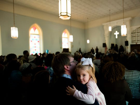 John McWilliams holds his daughter, Anna Elizabeth, 4, during the Dexter Avenue King Memorial Baptist Church Martin Luther King Jr. Birthday Service on Monday, Jan. 15, 2018, in Montgomery, Ala.