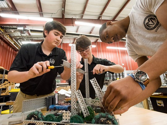 Brew Tech robotics competitors, from left, William Percival, Trevor Taylor, and William Sumlin work on a robot on on Friday, Feb. 2, 2018, in Montgomery, Ala. The team ranked 22nd in world after a competition in December.
