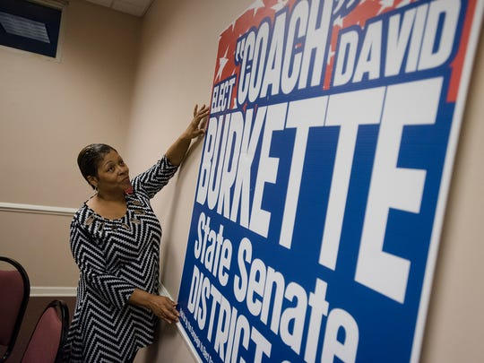 Jackie Weatherly hangs a David Burkette campaign sign
