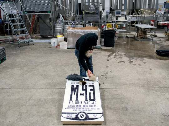 Old Nation Brewing Company employee Marcus Dixon setups up a game of bean bags with the boards labeled with the M-43 logo after work on Wednesday, Feb. 28, 2018, in Williamston.