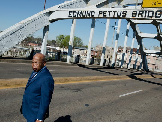 Congressman John Lewis stands on the Edmund Pettus