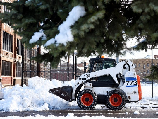 A bobcat clears snow around Memorial School in Passaic.