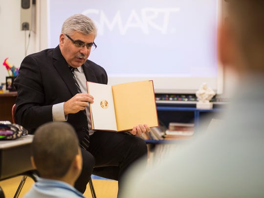 """St. Clair County Probate Judge John Tomlinson reads from Max Lucado's """"You Are Special"""" at Holy Cross Catholic School Wednesday, March 21. The children's book follows the story of a wooden Wemmick named Punchinello, who's concerned about what other Wemmicks think of him after only receiving gray dot stickers instead of gold stars from them."""
