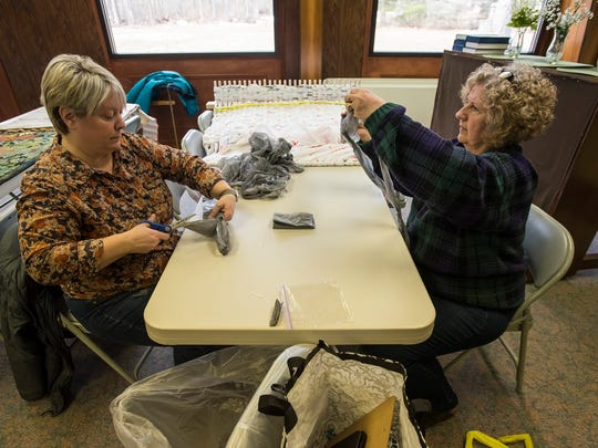 Colonial Woods Missionary Church Pastor Ann Harrington, left, cuts the ends off of a plastic shopping bag while Joan Watt ties them into long strands inside Lakeshore Presbyterian Church March 21. The strands of shopping bags, known as a plarn, will be put on a loom and woven into mats to be donated to the homeless.