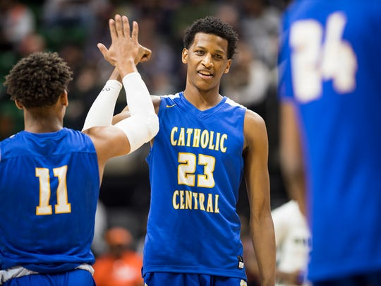 Grand Rapids Catholic Central High School player Marcus Bingham Jr. (23) high-fives Darrell Belcher before the MHSAA Class B basketball semifinals against New Haven High School at the Breslin Center in East Lansing Friday, March 23.
