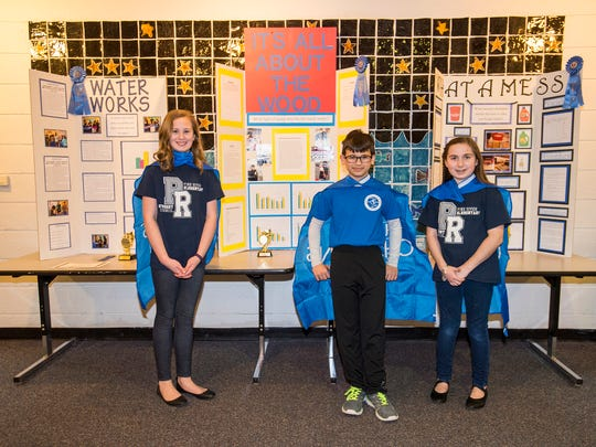 Pine River Elementary School students Rylee Schneider, 10, left; Cameron Spezia, 10, center, and Emma Terhune, 11,  stand with their science projects Wednesday, March 28. The students recently competed in the Flint Regional Science Fair.