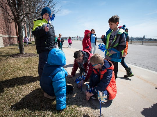 A group of kids in the YMCA's Spring Break Holiday Camp plant blue pinwheels outside of the YMCA Monday, April 2. The pinwheels are provided by the St. Clair County Child Abuse/Neglect Council to be planted in flowerbeds throughout downtown to raise awareness for child abuse.