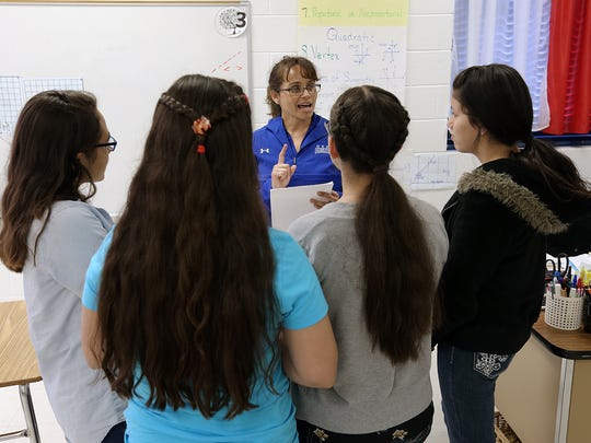 Clint Early College Academy math teacher Carlota Alvarez Basurto gives feedback to a group on their math project during her conference period Wednesday.
