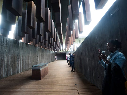 Visitors take pictures inside EJI's National Memorial
