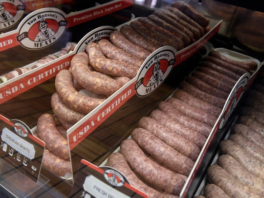 Fresh bratwurst in several flavors fill a display case