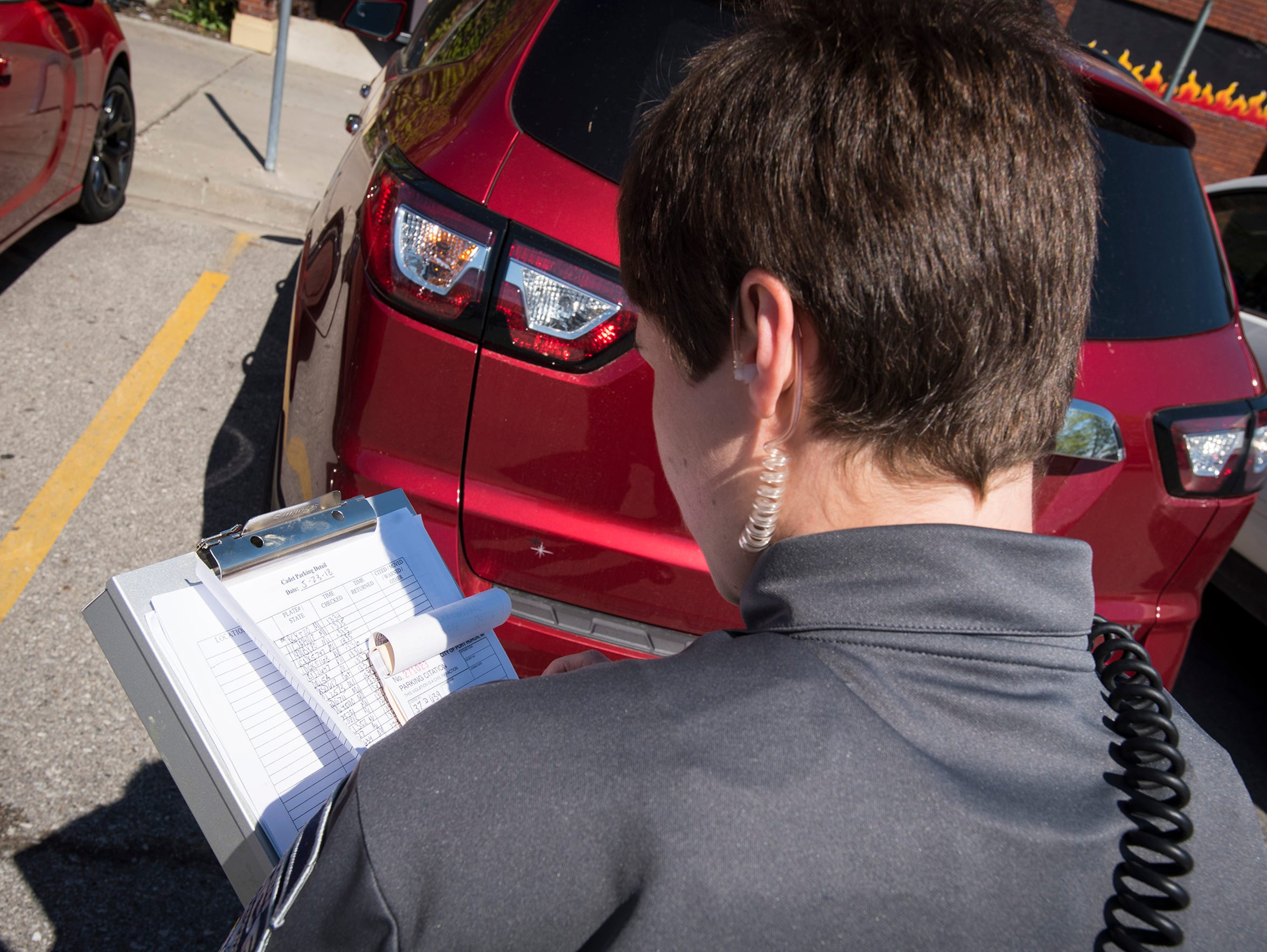 A Port Huron Police cadet fills out a parking ticket