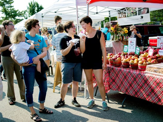 Morgan Doherty, left, and Amanda Niven, right, stood in front of the Country Mill Farms booth in fall 2017 in support of the LGBTQ community at the East Lansing Farmer's Market. Country Mill Farms returned to the market on Sept, 17, 2017 after the city banned the business.