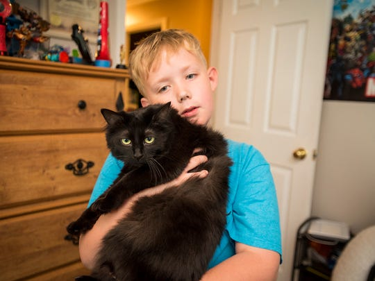 Linkyn Oliver, 9, holds his 2-year-old cat Cupcake