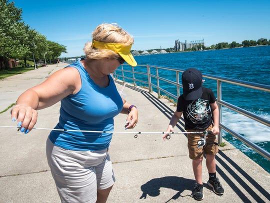 Tammy Beebee, left, helps her grandson Julian Gladstone,