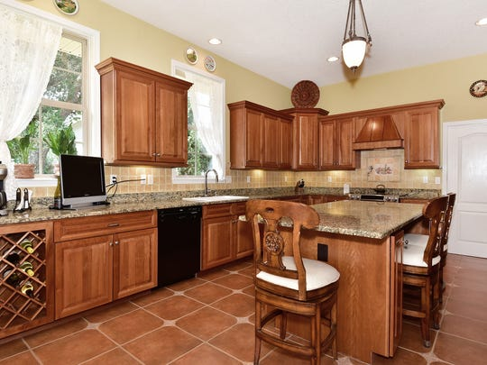 1076 Old Trail, the open kitchen with a large island and a wine rack.