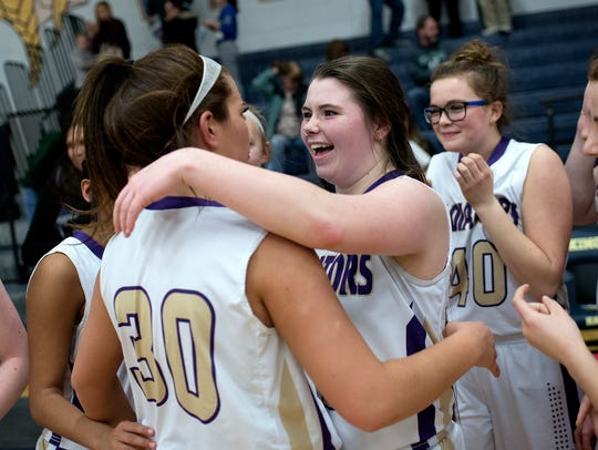 Jackie Jarvis, right, hugs Fowlerville teammate Grace