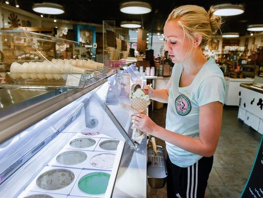Ally Koopman schöpft einen Pistazienwaffelkegel für einen Kunden bei Fudgin Delicious Ice Cream und Hom Decor Dienstag, 19. Juni, im Crossroads Center.