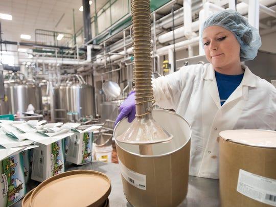 MSU food science senior Jordan Kietzman fills three-gallon jugs with Dantonio's Double Fudge Fake ice cream, Tuesday, July 25, 2018, at the MSU Dairy Plant in East Lansing.