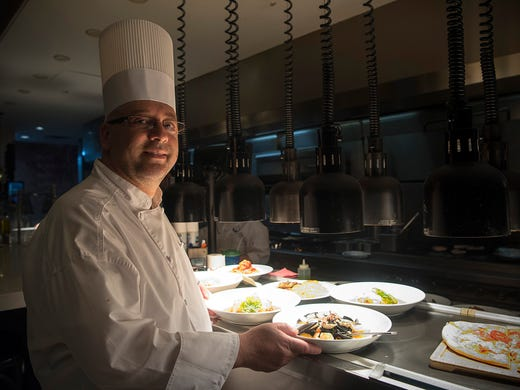 Chef Gianluca Sciagata stands with some of his creative