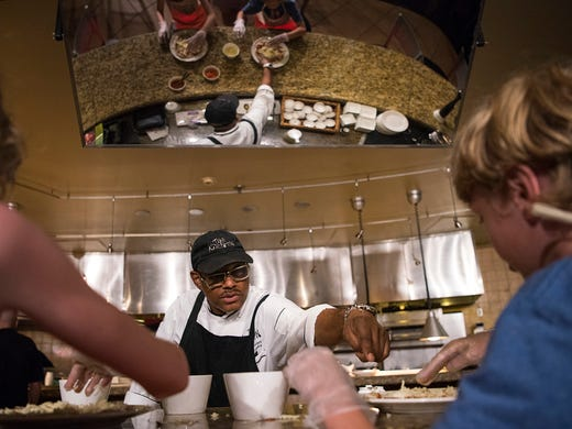 Chef Linwood Manley helps kids top off their own hand-made